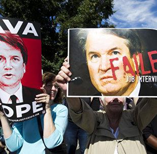Manifestantes con las fotos de Brett Kavanaugh, candidato al Tribunal Supremo