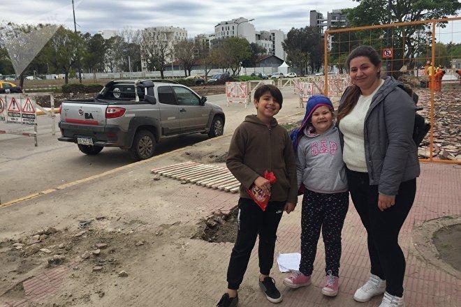 Niños posan ante los edificios construidos para albergar a los atletas de los Juegos Olímpicos de la Juventud que tendrán lugar en Buenos Aires
