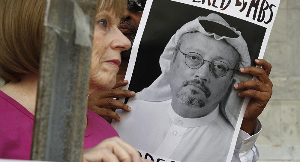 Personas con retratos del periodista saudí Jamal Khashoggi protestan en Washington