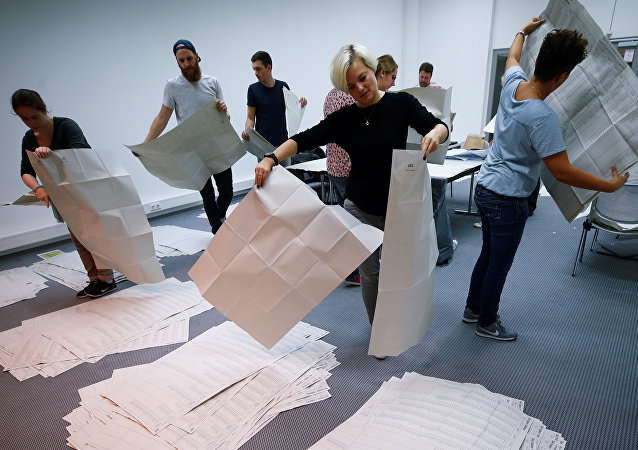 Los funcionarios electorales clasifican las papeletas de votación después de la conclusión de la votación en las elecciones estatales de Baviera en Múnich, Alemania.