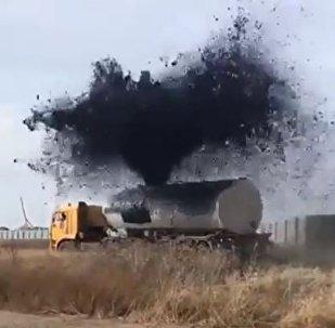 Una fuente de betún hirviente se vierte de un camión cisterna