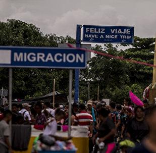 Migrantes en el puente internacional entre Guatemala y México intentan cruzar para pedir el asilo mexicano
