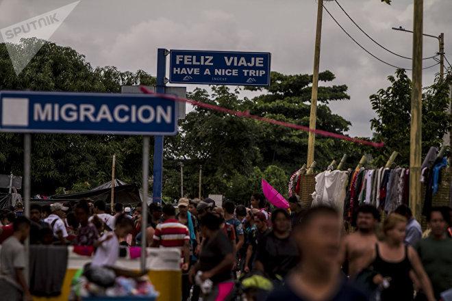 Miles de personas migrantes en el puente internacional entre Guatemala y México intentan cruzar para pedir el asilo mexicano