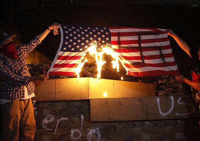 Dos personas están quemando una bandera de Estados Unidos durante una protesta a favor de la caravana de migrantes frente a la embajada estadounidense en Tegucigalpa, Honduras