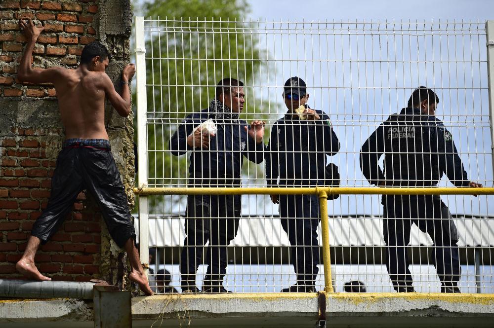 Un migrante hondureño, que se dirige a Estados Unidos, preparándose para saltar al río desde el puente fronterizo entre Guatemala y México.