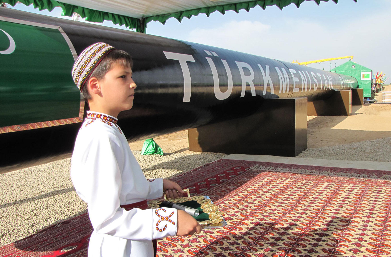 Un niño turkmeno vestido tradicionalmente espera al presidente Gurbangulí Berdimujamédov durante la ceremonia de inauguración de un gasoducto en 2010