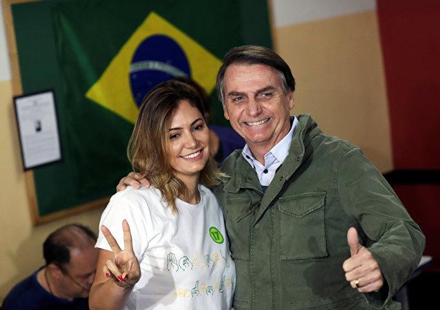 Jair Bolsonaro, candidato a la Presidencia de Brasil, posa al lado de su esposa, Michelle, tras votar