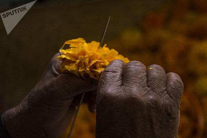 Un hombre fabrica listones de flor de cempasúchil para recibir a los difuntos durante el día de muertos