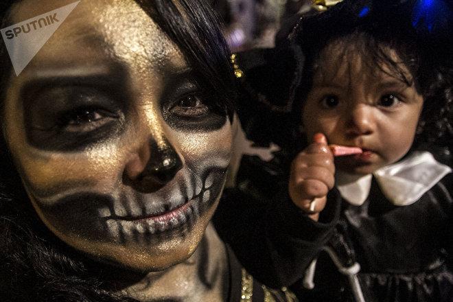 Una mujer y su hija maquilladas de catrinas durante el festejo del día de muertos