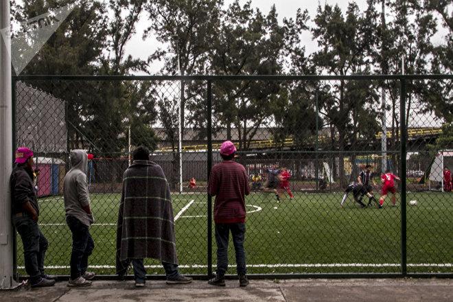 Integrantes del éxodo centroamericano miran un partido de fútbol entre Liverpool y Cuervos, en el deportivo de la Magdalena Mixhuca