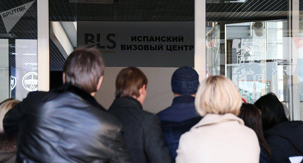 Personas esperan cerca del cerrado centro de solicitud de visados para España