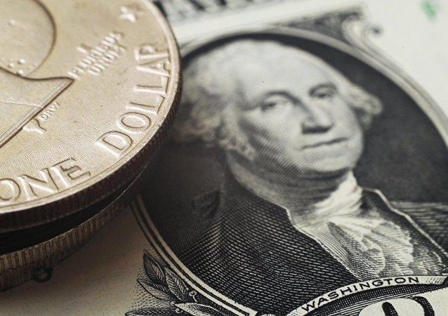 Un billete y unas moneda de dólares estadounidenses