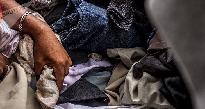 Una mujer de la segunda caravana del éxodo centroamericano busca prendas que estén en buen estado