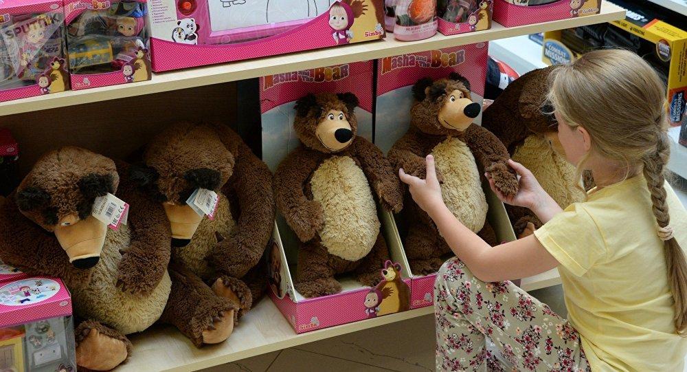 Una niña con juguetes del dibujo animado Masha y el oso en una tienda infantil