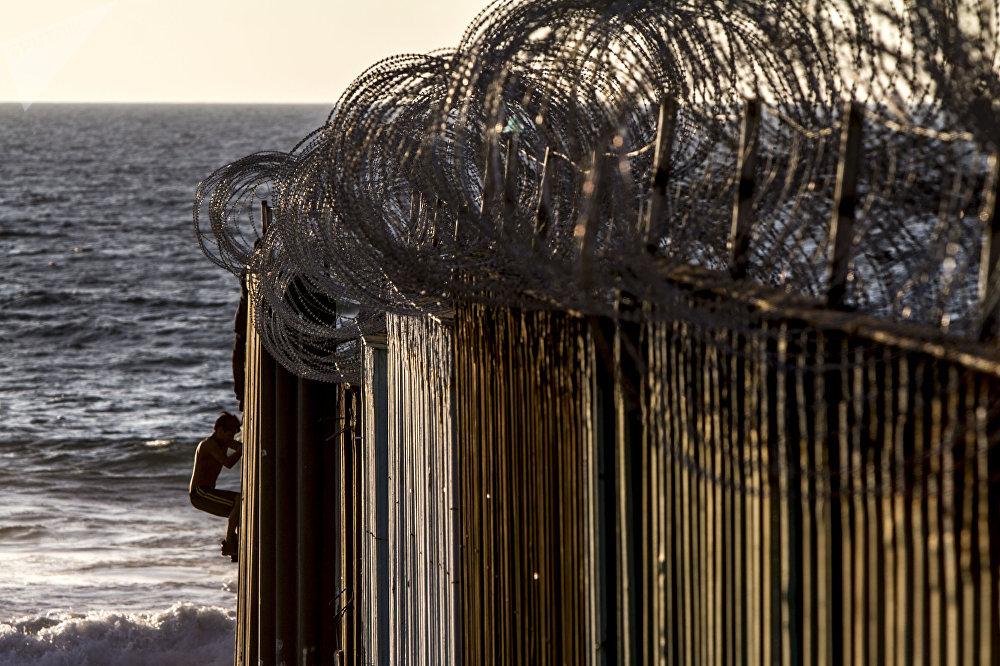 Dos jóvenes se suben al muro de playas de Tijuana después de que el Ejército estadounidense colocara alambre de púas el 13 de noviembre del 2018