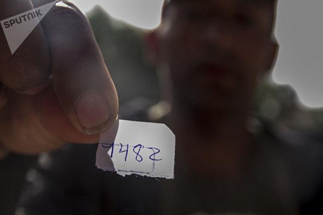 Billy Noel muestra el papelito que le dieron al pedir turno para solicitar asilo en el cruce fronterizo de San Ysidro