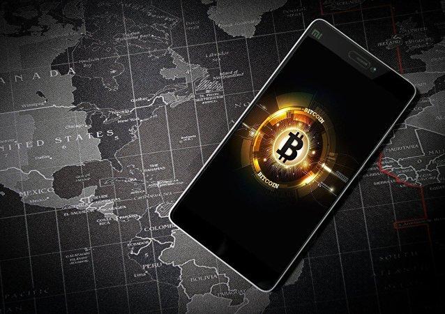 Un móvil con la imagen del logo de bitcoin