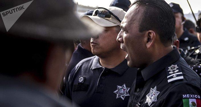 Un policía federal mexicano, Juan Carlos Morán, impide el paso de la manifestación centroamericana a la frontera con EEUU en el paso peatonal el Chaparral