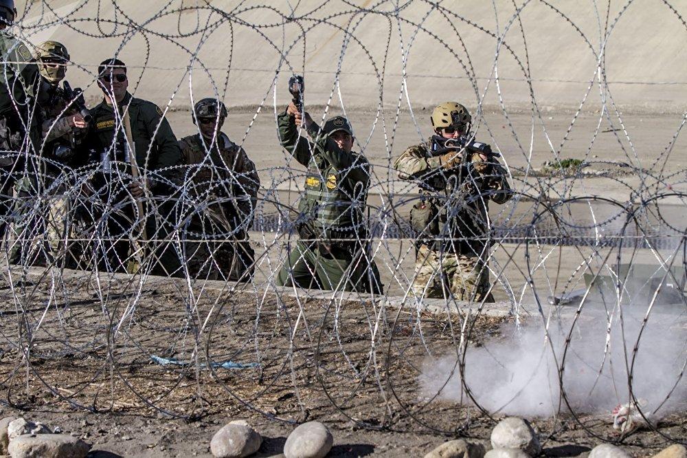 W. Lopez y D. Cody oficiales de la USBP (border patrol) disparan gases lacrimógenos contra la manifestación de centroamericanos en territorio mexicano