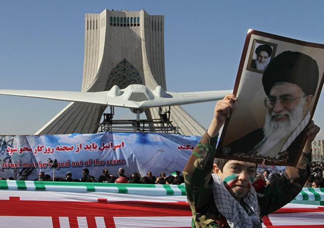 Un niño iraní sostiene el retrato del líder supremo de Irán ante la réplica del dron RQ-170 estadounidense capturado en 2012.