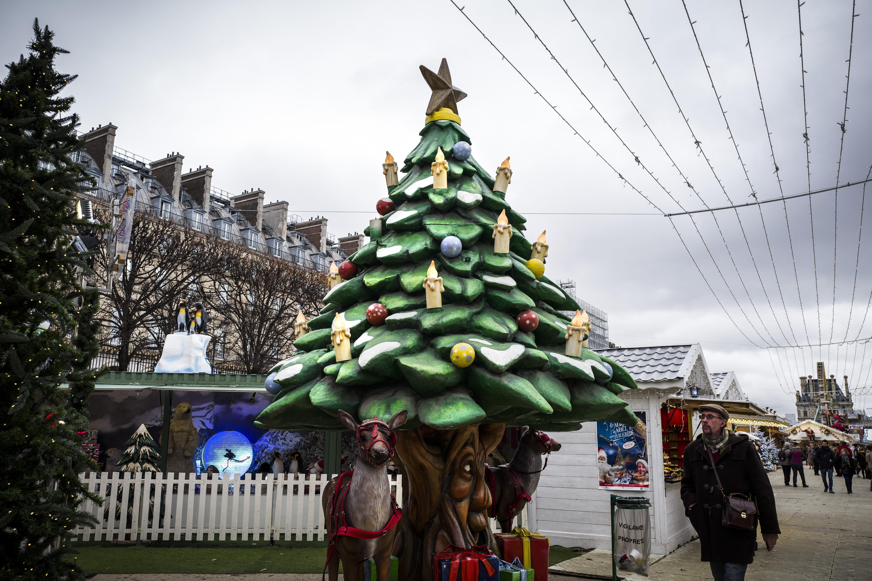 Un hombre pasa junto a un árbol de Navidad en un mercado de Navidad en el Jardin des Tuilleries (Jardín Tuilleries), en París