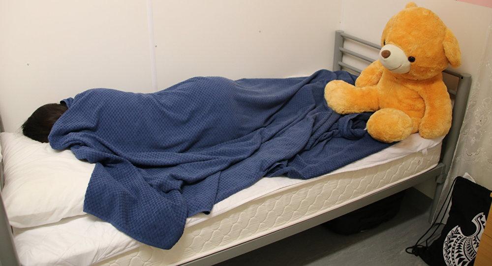 Una niña iraní de 12 años descansando en una cama en un centro de detención en Nauru, después de haberse intentado suicidar con gasolina