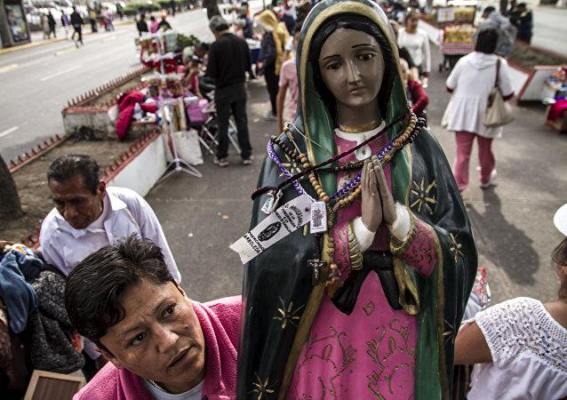 Mujer camina con una estatua de la Virgen de Guadalupe