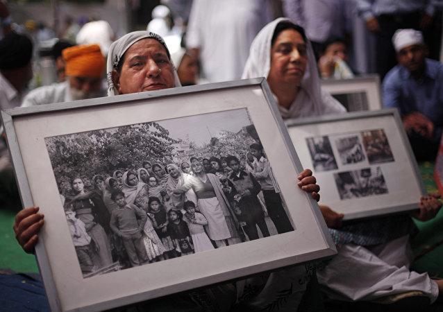 Las mujeres sij con las fotos de las víctimas de la masacre del 1984 contra los sijs