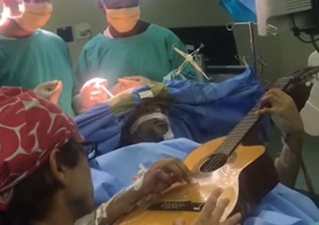 Un músico de Sudáfrica toca la guitarra durante una operación quirúrgica