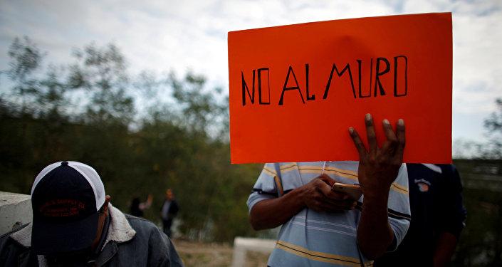 Un inmigrante sostiene una pancarta que dice 'No al muro'