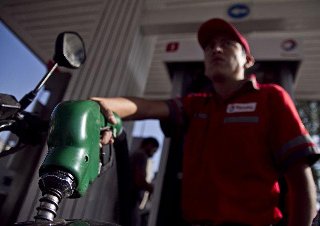 Trabajador de una gasolinera llena el tanque de una motocicleta