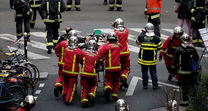 Los bomberos llevan a un herido en la explosión en París