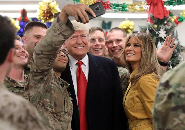 Donald Trump, presidente de EEUU, y su esposa, Melania, posan para una foto al lado de soldados estadounidenses en Irak