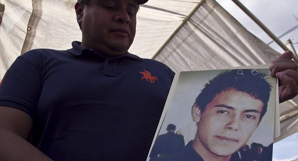 Hermano muestra la fotografía de Cesar Uriel Peña Linares de 23 años desparecido tras la explosión de un ducto de Pemex que dejó al menos 79 personas fallecidas