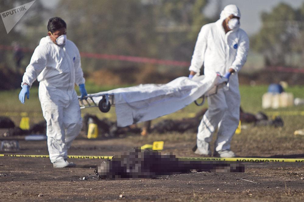 Cuerpos calcinados son inspeccionados por peritos tras la explosión de un ducto de gasolina de Pemex