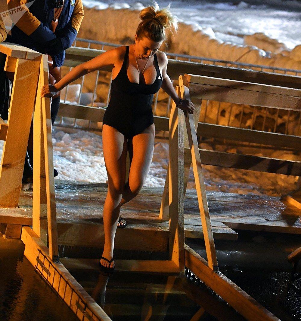 Una mujer se prepara para zambullirse en un lago en Vladivostok
