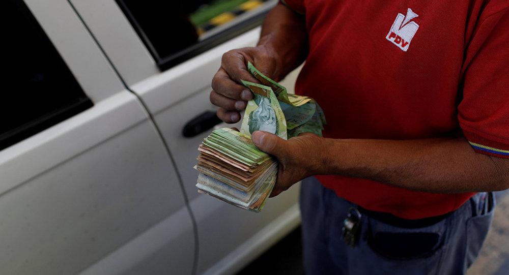 Bolivares venezolanos en las manos de una empleada de PDVSA