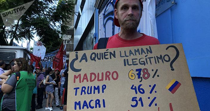Una persona con una pancarta durante la vigilia antiimperialista frente a la Embajada venezolana en Buenos Aires