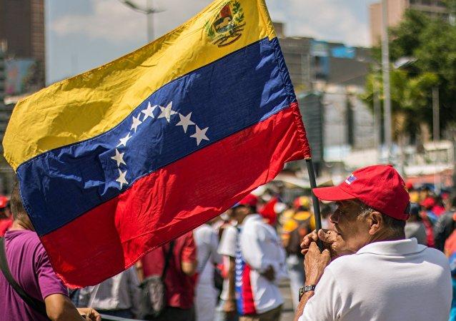 Un hombre con la bandera de Venezuela
