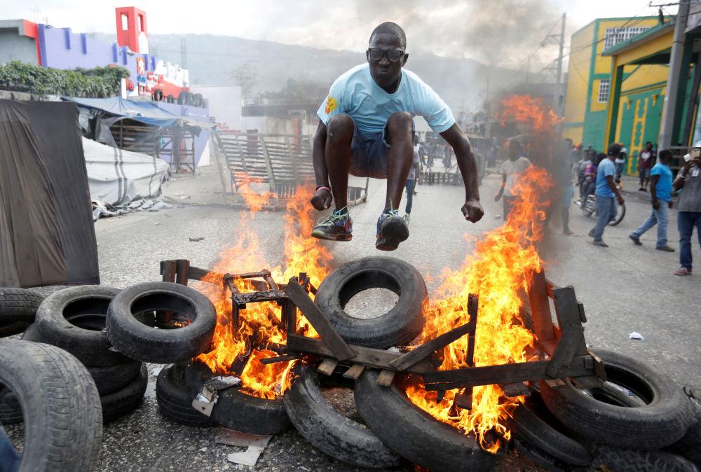 Un manifestante saltando encima de una barricada en llamas durante una protesta contra el Gobierno en Haití.
