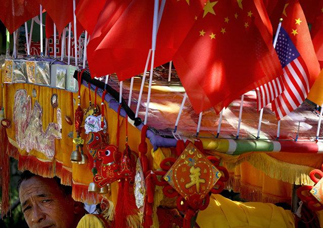 Un conductor mira desde su trishaw decorado con una bandera americana y una china en Pekín