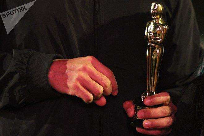 Vecino de la colonia Roma carga una estatuilla de los premios Oscar.