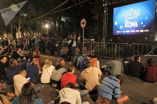Vecinos de la colonia Roma miran la entrega de los premios Oscar en la plaza Río de Janeiro.