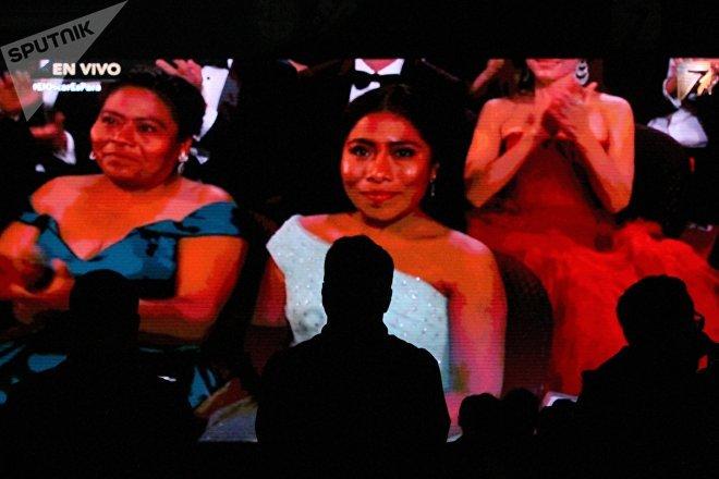 Un hombre en la proyección de los premios Oscar, de fondo ve a Yalitza Aparicio junto a su madre en la premiación de los Oscar 2019.