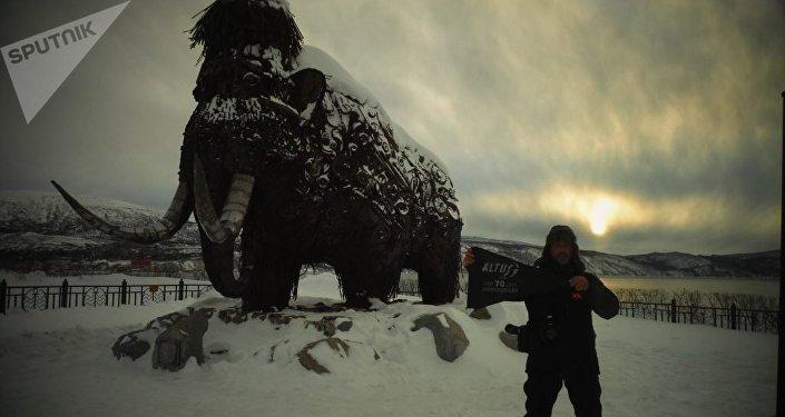 Andrés con la escultura del mamoth en Magadán