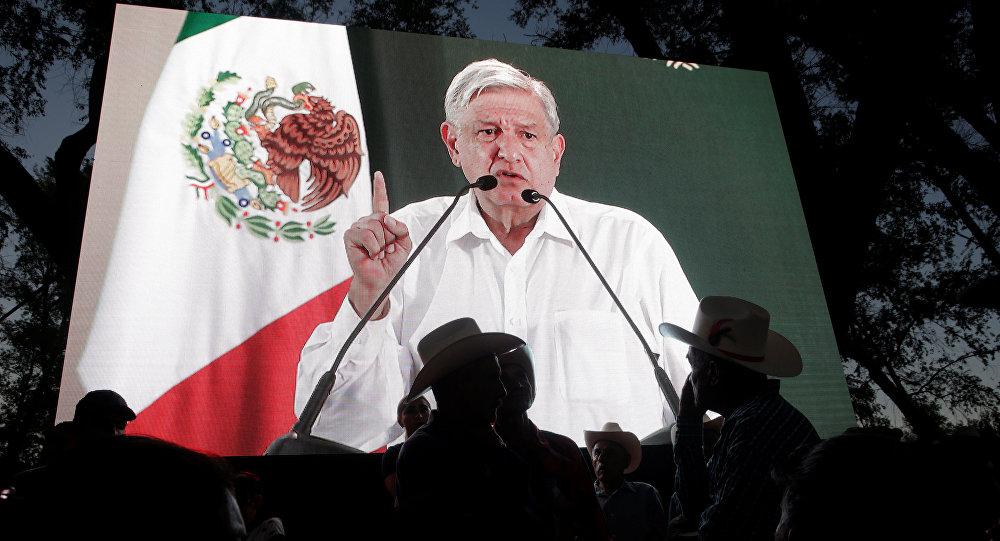 Andrés Manuel López Obrador da un discurso y aparece en una pantalla