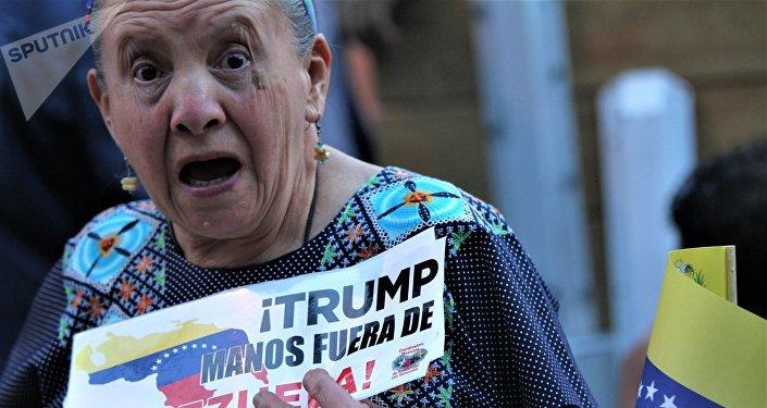 Mujer con carteles contra la intervención de EEUU en Venezuela participa de una marcha en la Ciudad de México