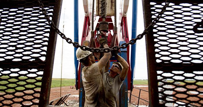 Dos empleados trabajan en una grúa petrolera en EEUU