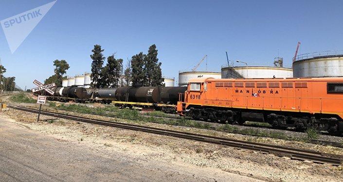 Una locomotora junto a instalaciones de procesamiento de soja en una terminal portuaria del Gran Rosario, Argentina