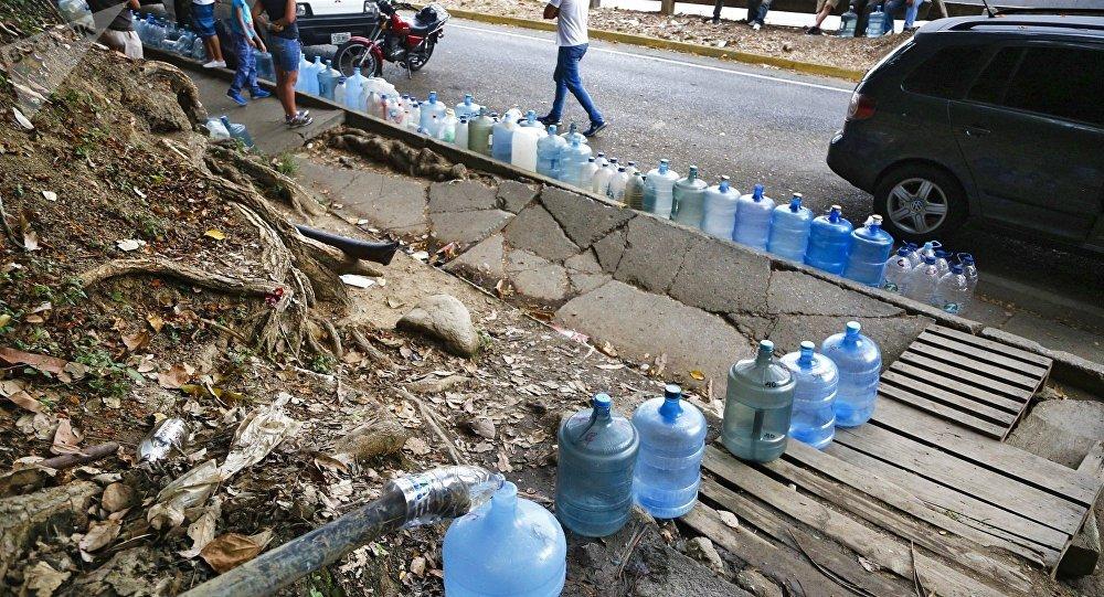 Venezolanos rellenan botellas de agua durante apagón en Caracas